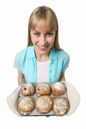elevated portrait of a woman holding a tray of muffins