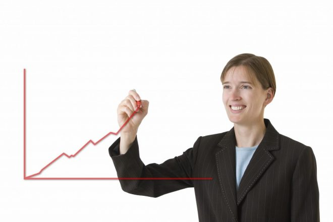Young business woman in a tailored suit drawing a chart showing steady growth. Image is isolated on a white background.