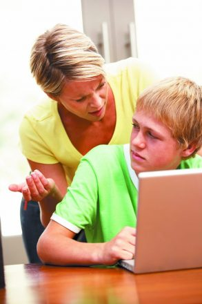 Angry Mother And Teenage Son Using Laptop