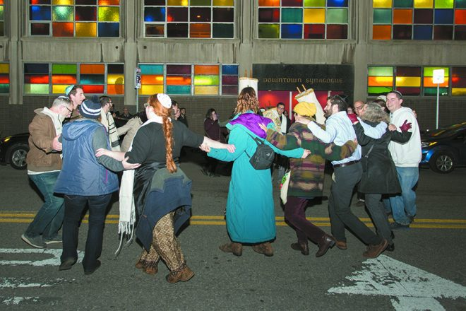The singing and dancing with the Torahs moves outside.