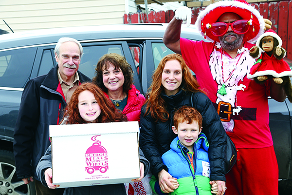 Dan and Sue Stettner and Elyse, Ava and Ryan Cohen, all of Huntington Woods, and Eric Harris of Detroit (dressed as Santa) deliver meals for Bridging Communities in Detroit