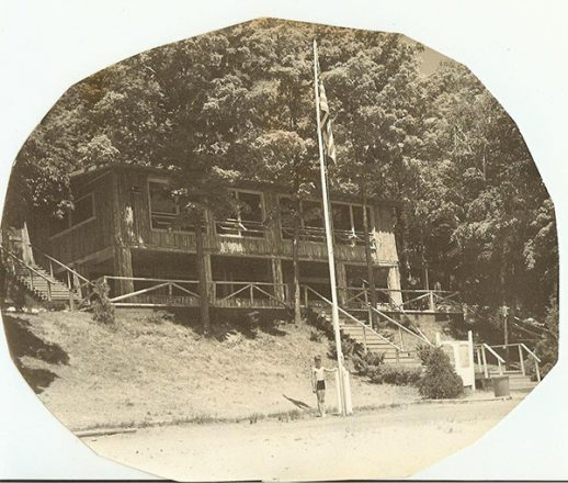 In this historic photo, a lone camper stands at the flag pole in front of the dining hall at Camp Sea-Gull