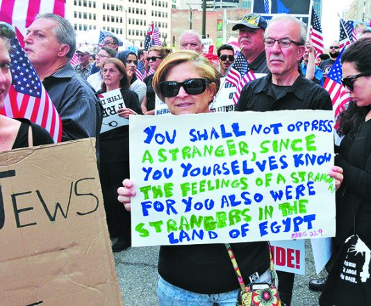 Lori Lutz, Detroit Jews for Justice, holds up a sign bearing a quote from Exodus at an anti-deportation protest on June 21  ahead of the ACLU lawsuit aimed to slow the deportation procedures of Iraqi Christians living in Metro Detroit.