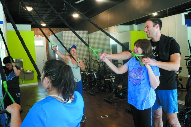 Fuse45 co-owner Jeffrey Friedman works with Lauren on the resistance bands