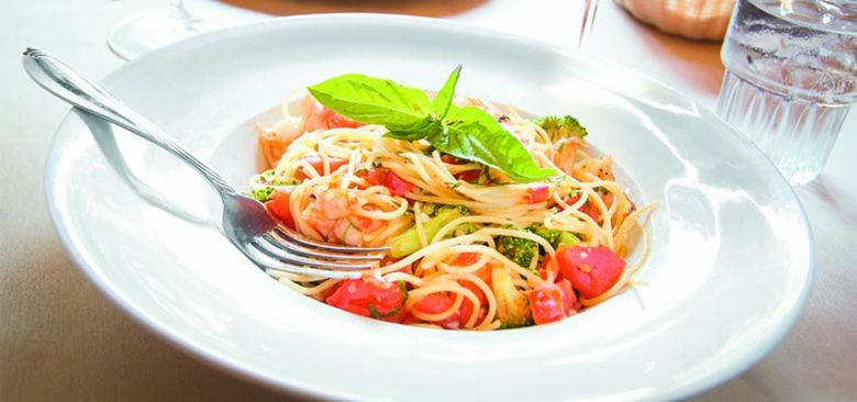 A delicious Italian meal of spaghetti with shrimp and veggies.