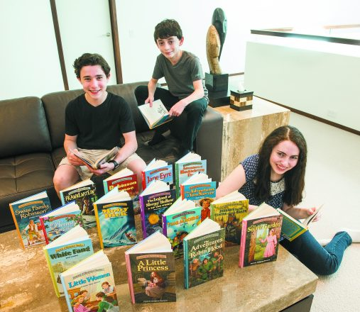 Jacob, 15, Reuben, 11 and Alana Blumenstein, 17, with all the books available on their KidsRead2Kids.com website