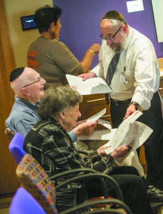 Rabbi Dovid Polter hands out information regarding the High Holidays. Resident Al Zack smiles as Evelyn Burton looks the material over.