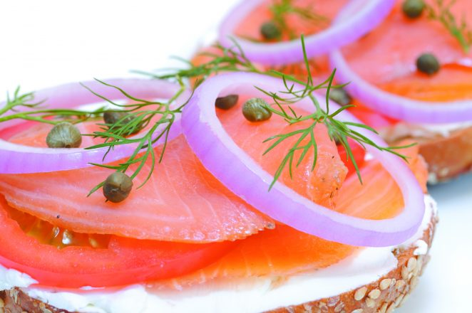 Bagel and smoked salmon, cream cheese, tomato, red onion, capers and dill. Close-up, isolated on white.