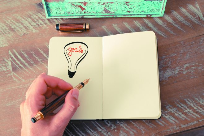 Retro effect and toned image of a woman drawing a lighting bulb with fountain pen on a notebook. GOALS symbol and concept, copy space available for text