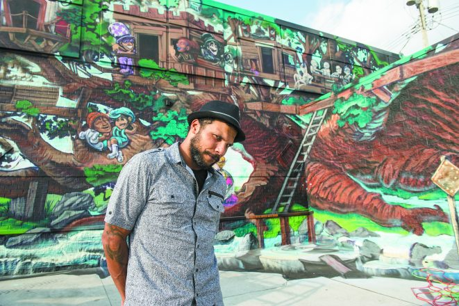 Artist Kobie Solomon with his mural.