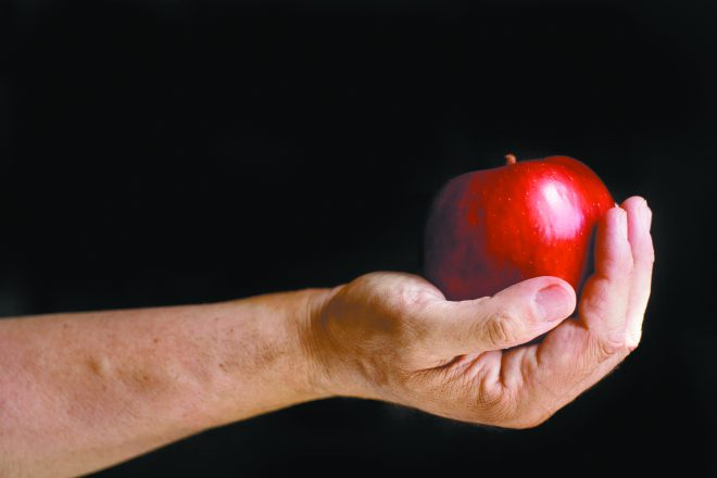 A man offering a red apple, isolated on black