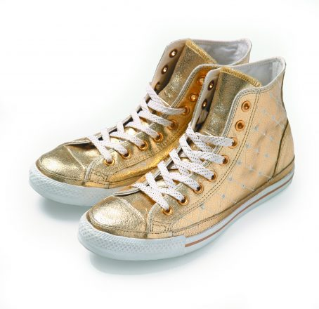 Golden vintage shoes on white background.