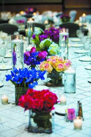 Multi-color centerpieces form a line down a table set for a wedding reception.