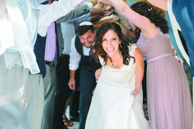 """After the ceremony, the newlyweds' friends """"deliver"""" them to the celebration and the hora."""