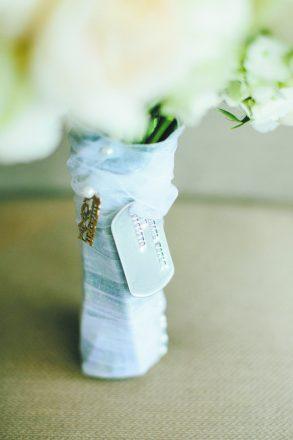 A military dog tag and woman's necklace are wrapped around a wedding bouquet.