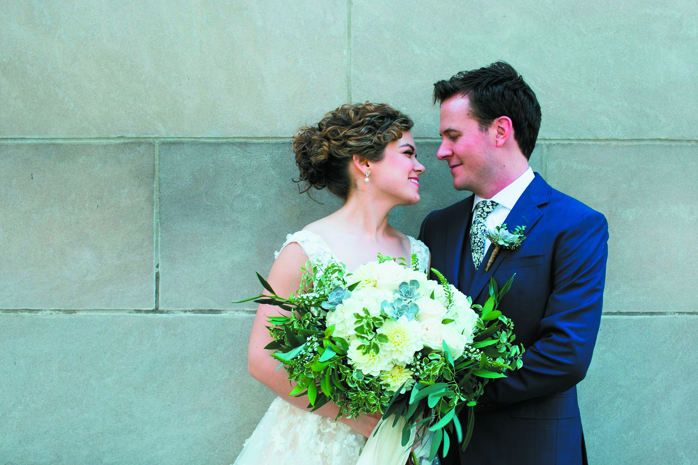 A bride and groom smile at each other before a brick wall. The bride is holding a large bouquet of white hydrangeas.