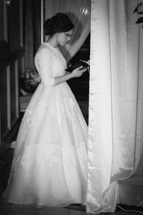 A bride reads from a siddur book on her wedding day.