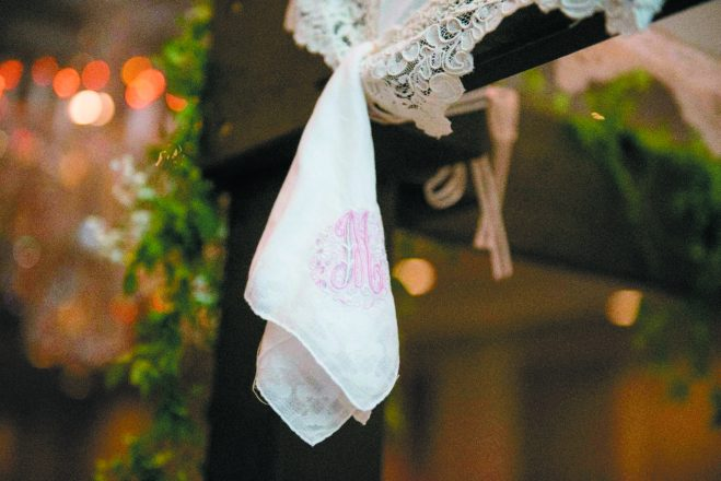 A pink and white handkerchief hangs from the top of a chuppah.