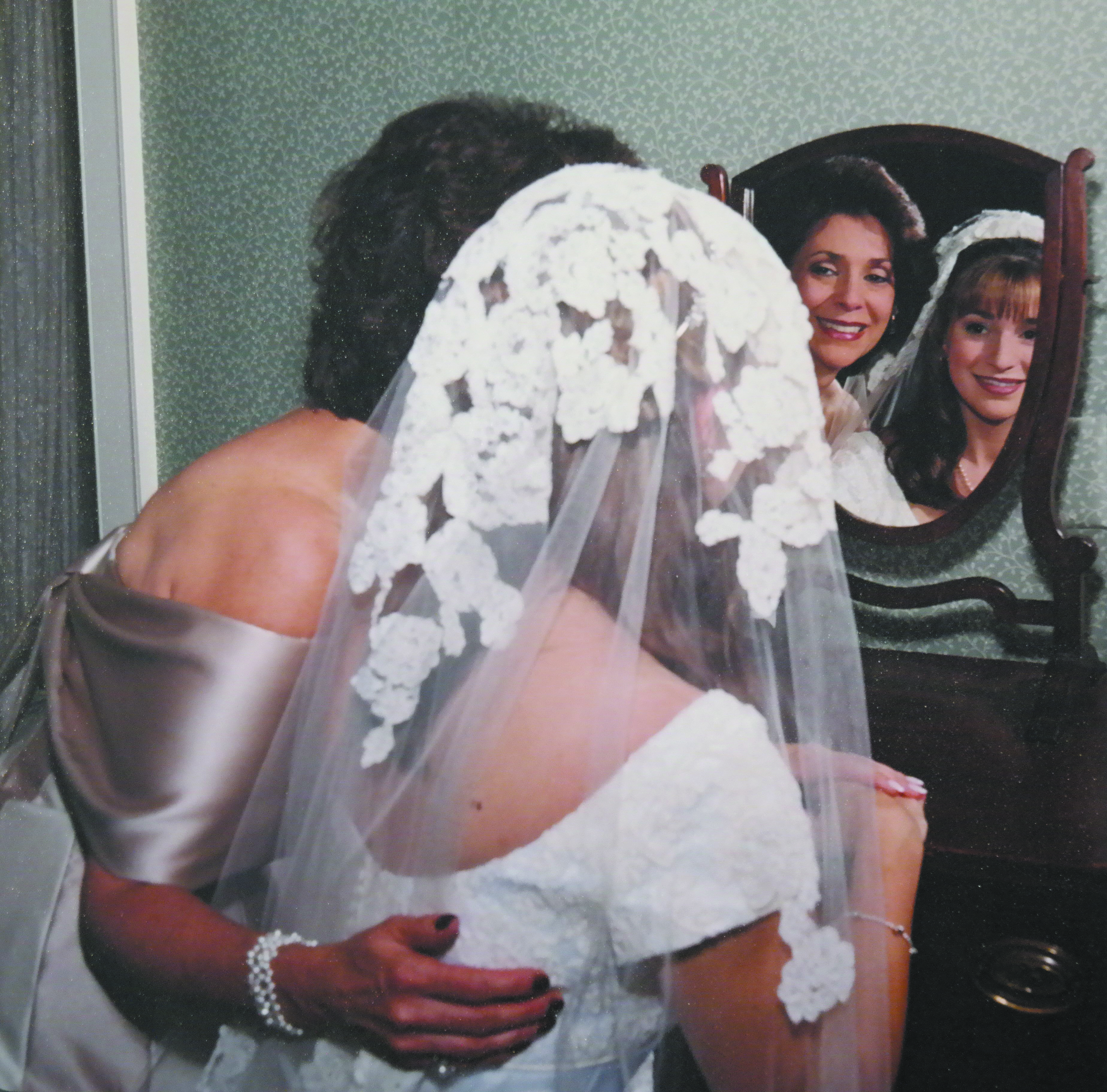 A bride and her mother stand before a mirror.