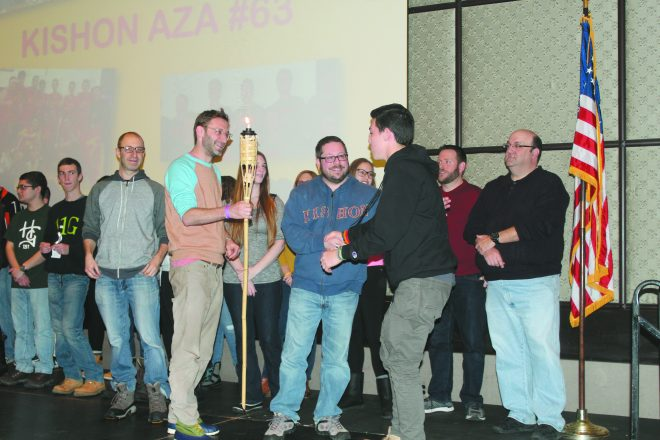 Max Rybak, president of Kishon AZA #63, right, receives a torch from Kishon alumni Andrew Ceifetz, Mark Snyder and Joel Snyder.