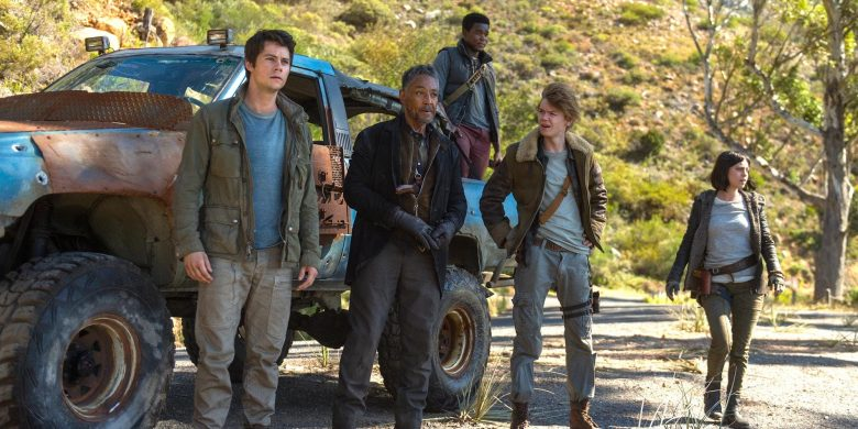 The image features characters from the movie Maze Runner: Death Cure. Three male characters stand in front of a large truck while one female character walks towards the men. One male character stands in the bed of the truck. All of the characters are looking off into the distance at something unknown.
