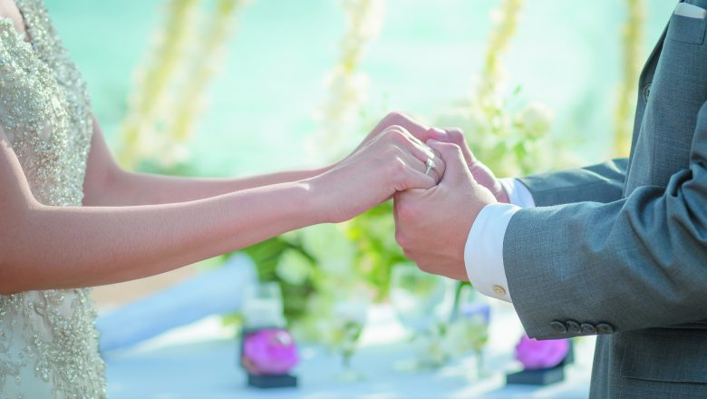 A man and a woman hold hands at a wedding ceremony.
