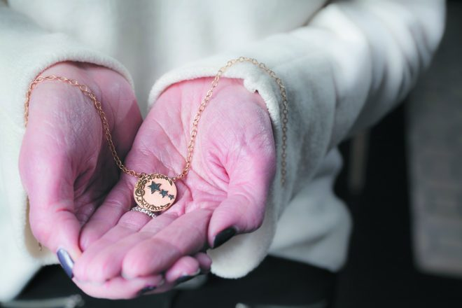 a necklace held in two hands. The necklace has a half-moon and music notes, and each start has one of Jamie Daniel's initials (JRD)