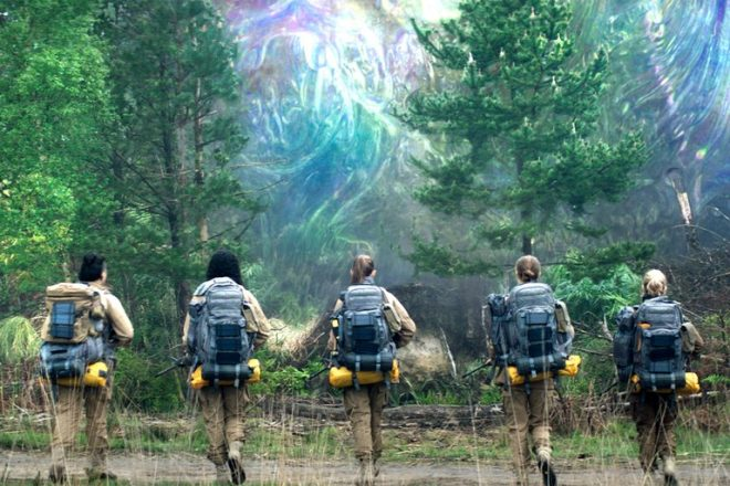 Still from the movie Annihilation. 5 women walk with backpacks on away from the camera.