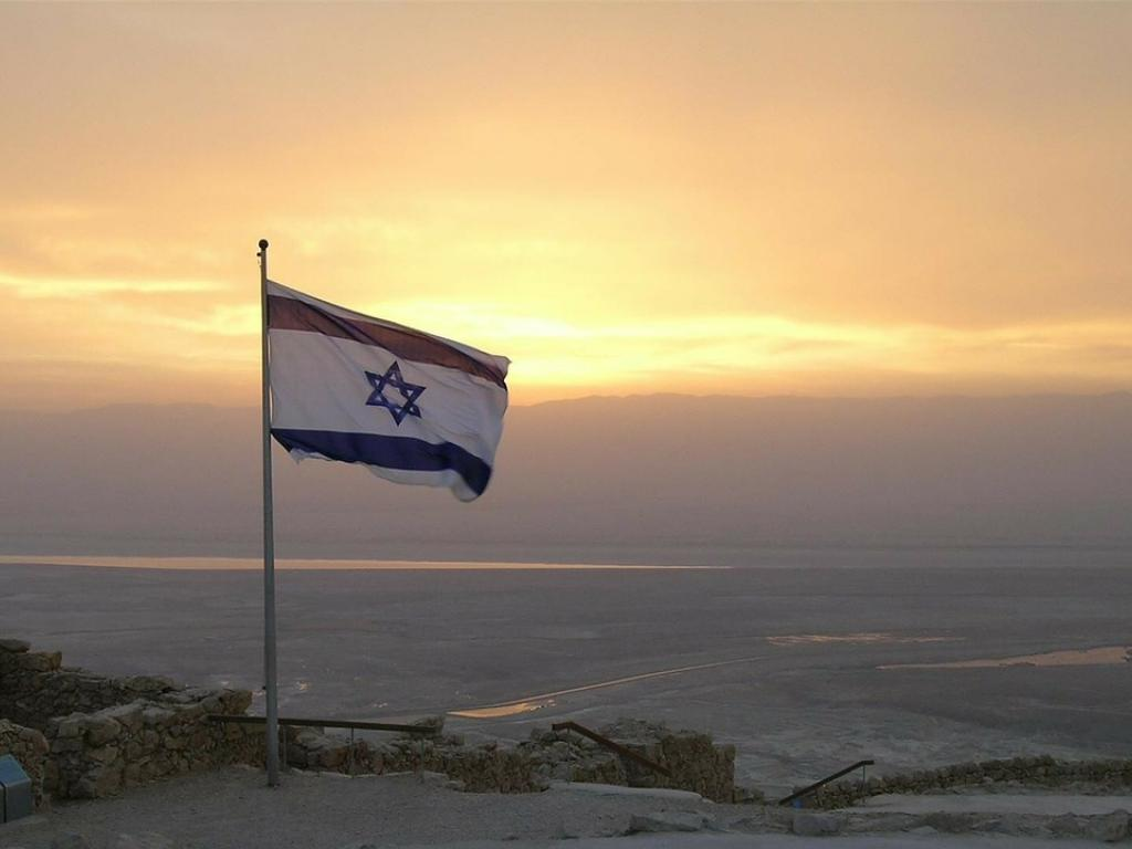 Israeli flag waves on top of a mountain in the sunset.