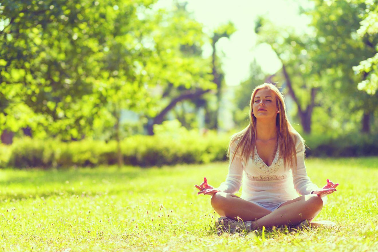 Beautiful young girl meditating in the park on a sunny summer day