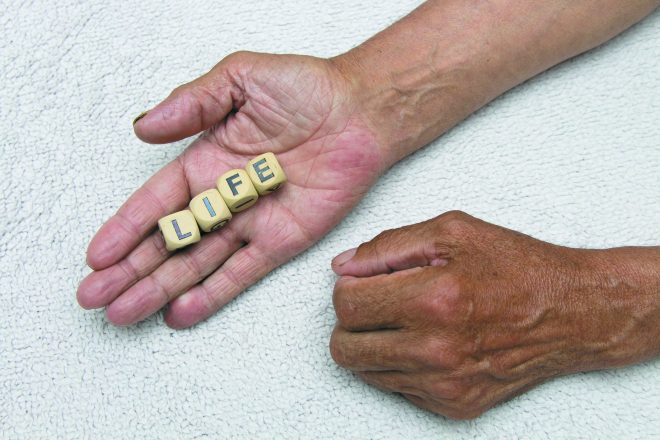 The elderly man is holding the dice with the inscription life. The concept of retirement.