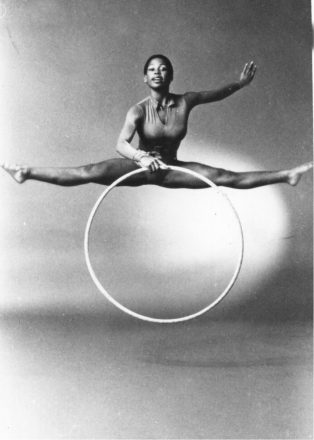 Wendy Hillard holds a hula hoop in the air while she does a leap, performing the splits.