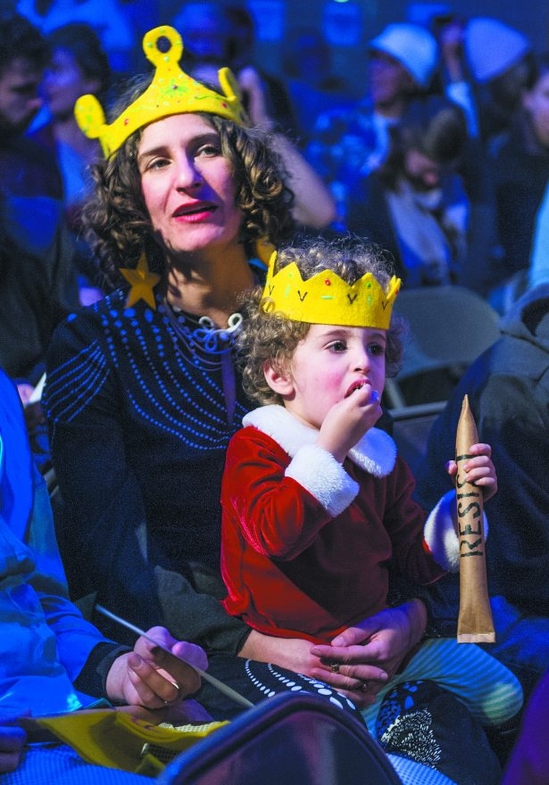 Sarah Pappas and Asa Berkow-Pappas, 2, watch the actors on stage.