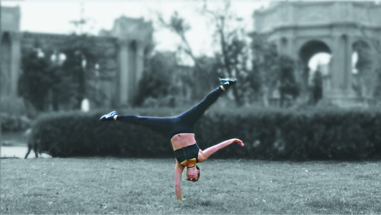 A woman performs a one-handed handstand with her arm out and legs spread in a split wearing a sports bra and leggings.
