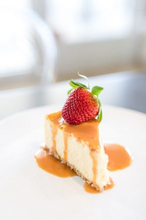A plate with a piece of cheesecake and a caramel sauce and strawberry on it.
