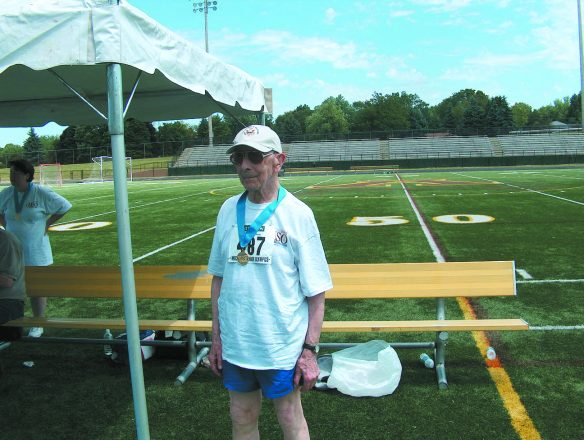 Manny Hauer shows off a 1,500-meter race walk gold medal he won in 2009 when he was 98 years old.