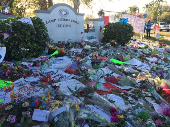 Flowers and signs lay in front of a sign for Marjory Stoneman Douglas High School in honor of the recent school shooting victims.