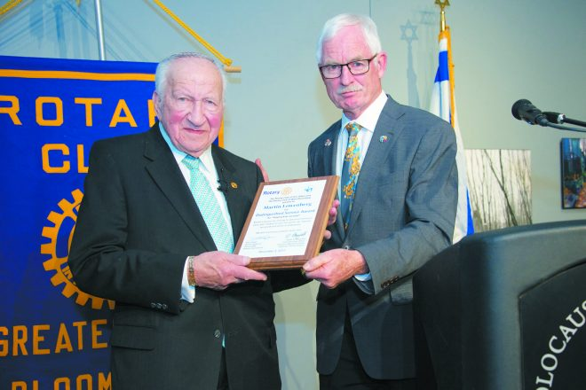 """Barry Fraser, district governor of Rotary District 6380, presents Holocaust survivor Martin Lowenberg with the Distinguished Service Award Dec. 3 at the Holocaust Memorial Center from Rotary Clubs of Ann Arbor and West Bloomfield. The award is the highest Rotary honor, given to those who have made significant contributions to the community. Lowenberg recounted his stories of survival and loss of family members during the Holocaust. """"Let us hope an event like the Holocaust never happens again. I always say, 'Hate hurts, but love heals,'"""" he said."""
