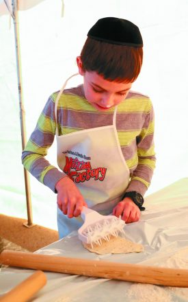 Yosef Litenatsky, 9, of Oak Park works on his matzah.
