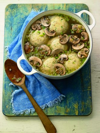 Apot of matzo ball soup with mushrooms and jalapenos on a table cloth with a wooden spoon. Popular among Mexican Jews.