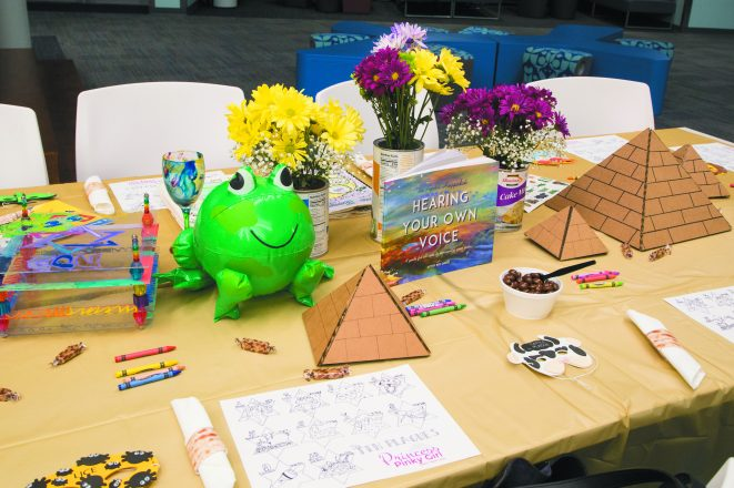 """The Kids Table"" from the Pinterest event features paper pyramids, snacks, coloring options and flower vases made from empty Passover food containers."