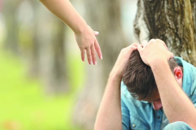 Sad teen sitting on the grass in a park and a woman hand offering help with a green background
