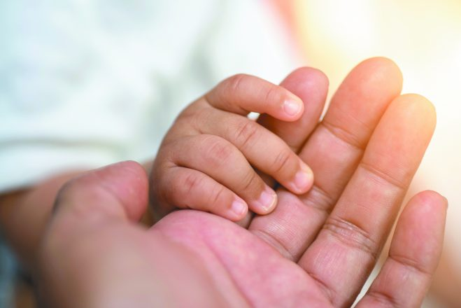 Baby hand holding mother's hands