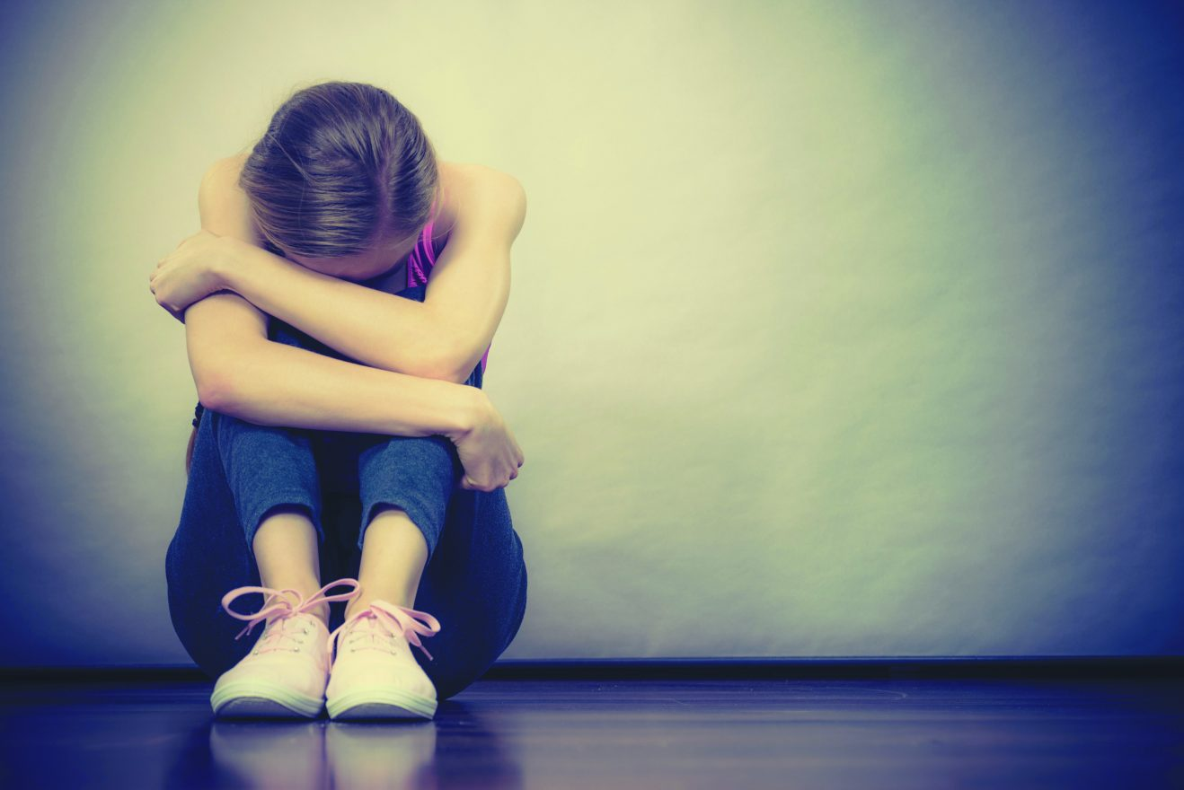 Sad depressed young teenage girl sitting by wall hiding face.