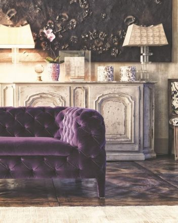 A neutral, rustic backdrop sparkles with modern jewel-toned purples. Find a similar tufted-velvet Chesterfield sofa at Wayfair.com.