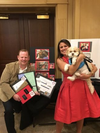 A man and woman pose with a dog and some photos of successful adoptions at Detroit Dog Rescue's Canines and Couture.