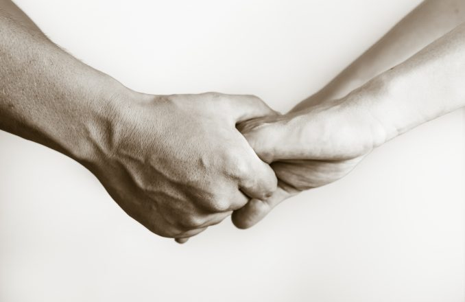 Two pairs of hands holding, and touching each other.