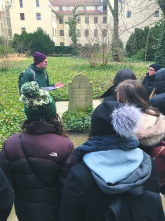 "The group's walking tour, titled ""Don't Trust the Green Grass,"" highlights the many open, grassy spaces in the city that appear unused and used to be important sites for Jewish Berliners. Visible in the green space right next to our hotel was the foundation of the first synagogue in Berlin. In this photo, the group visits what appears to be a lovely green park tucked away, but as visitors continue down the path, they see the headstone of philosopher Moses Mendelssohn, which remains standing in a lonely corner of the space. Closed in 1827, the cemetery was destroyed and desecrated by the Nazis in 1943. A group of us paused to say Kaddish to remember those who were buried here."