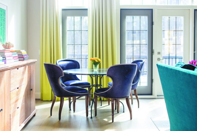 Anne Strickland of PORT Mfg. & Design used citrus-toned ombre draperies as an unexpected way to vertically fill this room with color.