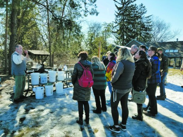 A volunteer shows participants how to turn sap into maple syrup.